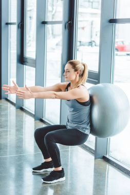 sportswoman exercising with fitness ball in gym