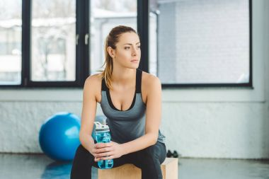 portrait of pensive sportswoman with water bottle looking away in gym