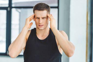 portrait of man in sportswear having headache