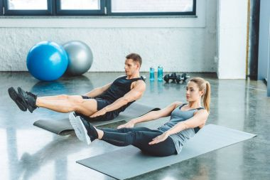 couple doing abs exercises on mats before workout in gym