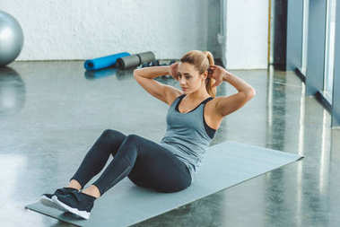 young sportswoman doing abs exercises on mat in gym