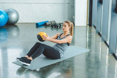 sportswoman doing exercises with ball in gym