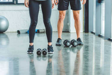 cropped shot of couple standing near dumbbells in gym