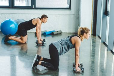 side view of couple in sportswear training with dumbbells in gym