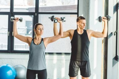 focused young man and woman exercising with dumbbells in gym