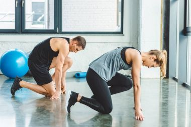 side view of sportsman and sportswoman working out in gym together