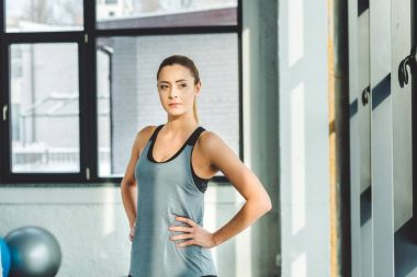 portrait of young caucasian woman akimbo in sportswear in gym
