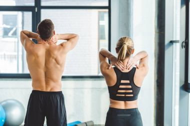 back view of couple warming up after workout in gym