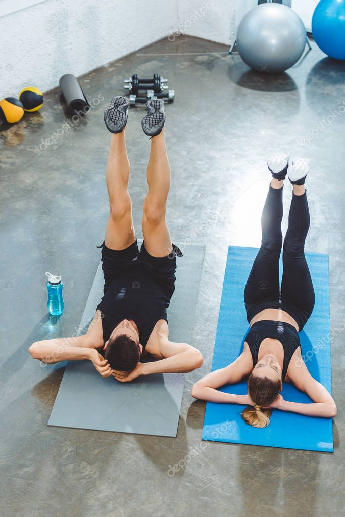 high angle view of sporty young couple exercising on yoga mats in gym