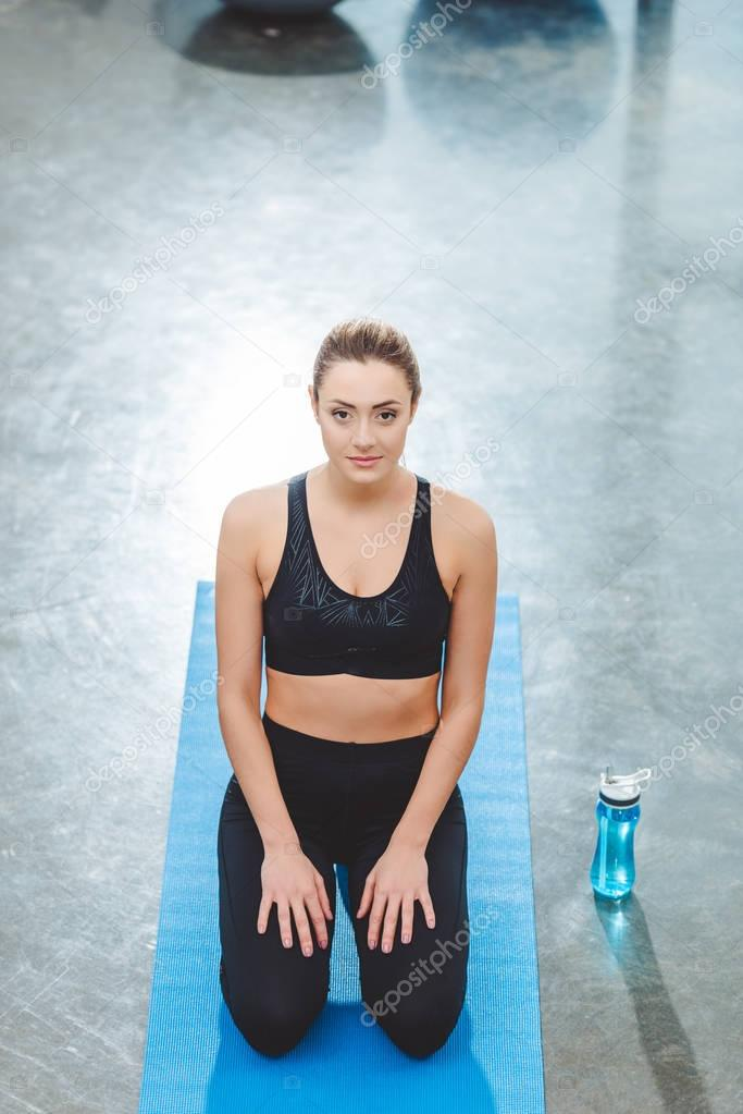 high angle view of young sportswoman sitting on yoga mat and looking at camera in fitness studio