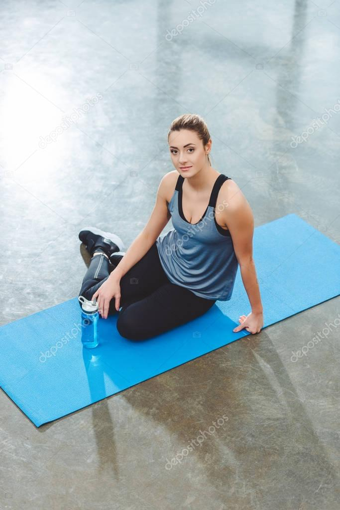 high angle view of young sportswoman sitting on yoga mat and looking at camera