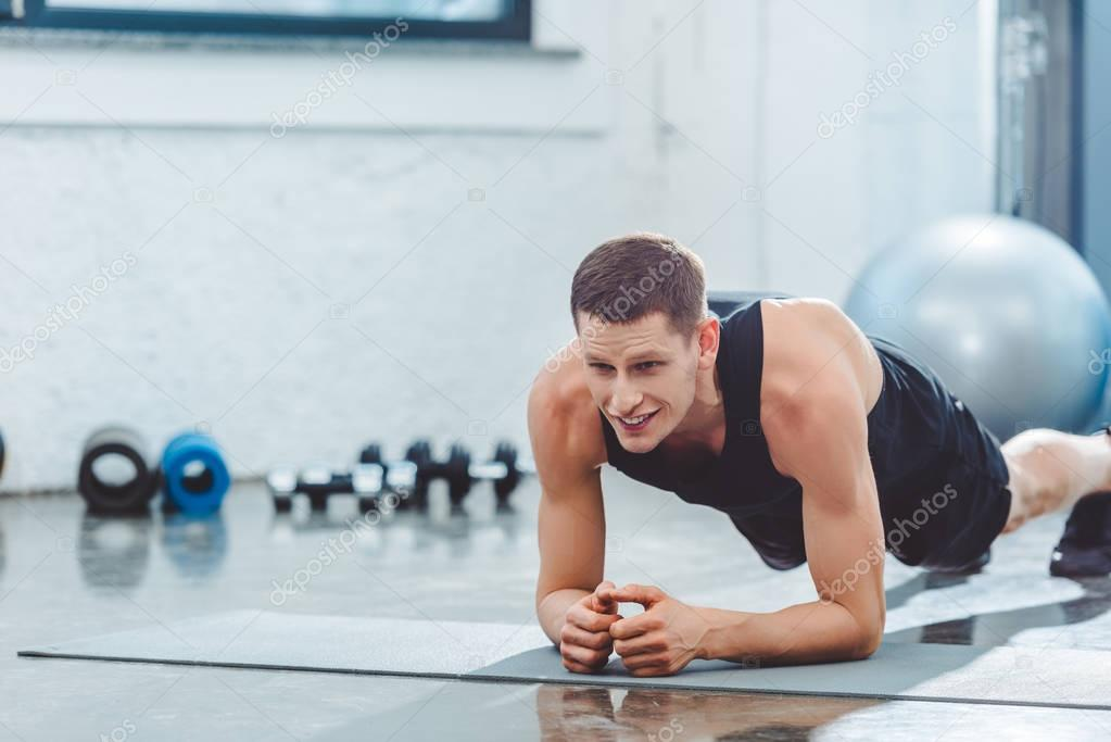 portrait of young sportsman working out on mat in gym