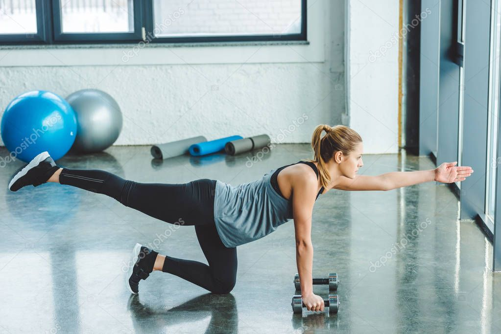 side view of sportswoman exercising with dumbbells in gym