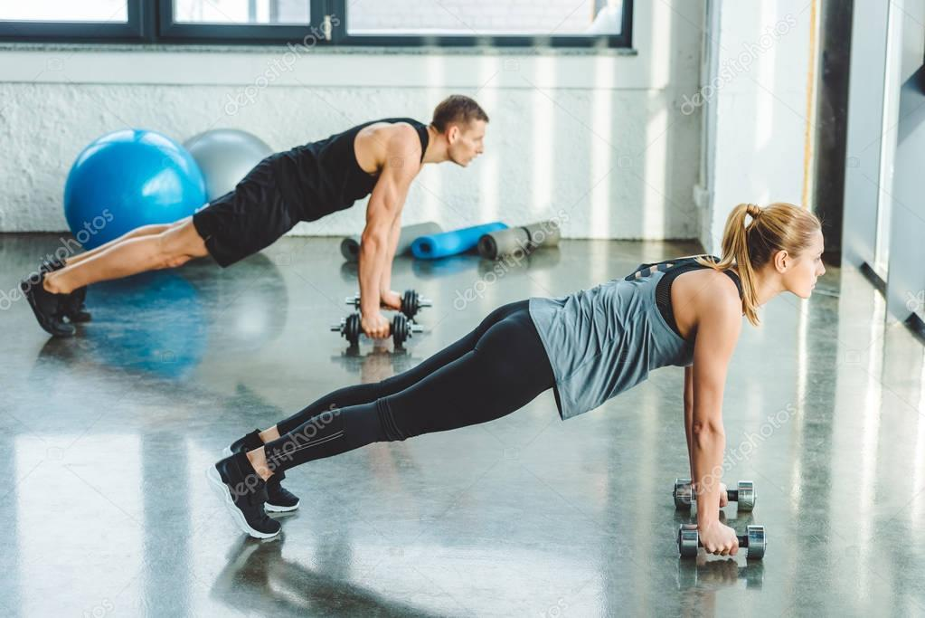 side view of young man and woman exercising with dumbbells in gym