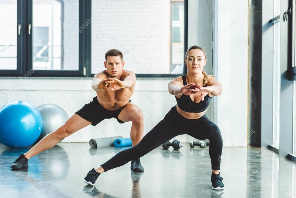 caucasian man and woman training in gym together