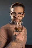 Photo close-up view of stylish young man in spectacles holding glass of whisky and looking at camera isolated on grey