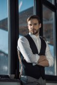 portrait of confident stylish young businessman standing with crossed arms and looking at camera