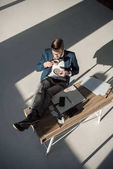 Fotografie high angle view of stylish young businessman in eyeglasses drinking coffee at workplace