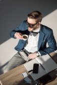 high angle view of smiling young businessman drinking coffee and looking away