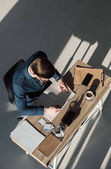 overhead view of stylish businessman writing in notebook at workplace