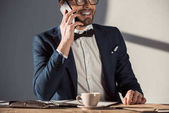 Fotografie smiling young businessman in eyeglasses and bow tie talking on smartphone