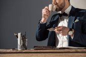 cropped shot of stylish young businessman drinking coffee at workplace