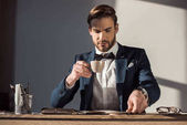 stylish young businessman drinking coffee at workplace
