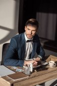 stylish young businessman writing in diary and looking away