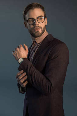 handsome stylish bearded man in wristwatch and spectacles looking away isolated on grey