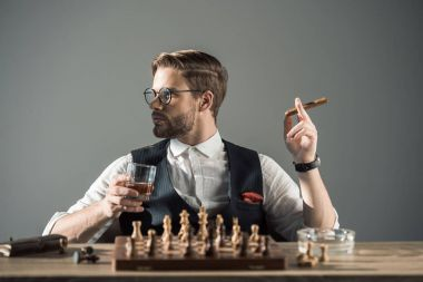 young man with glass of whisky smoking cigar and looking away while playing chess