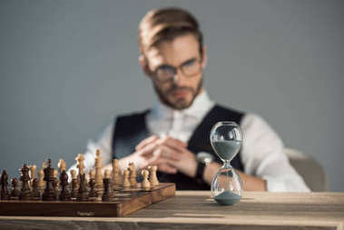 close-up view of chess board with pieces and sand clock on table and businessman sitting behind