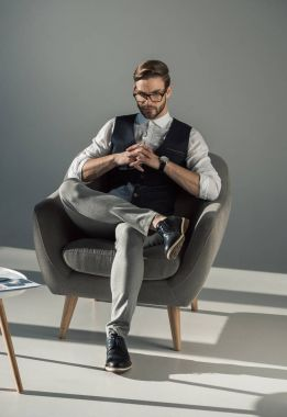 handsome stylish young businessman in eyeglasses sitting on armchair