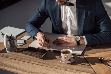 cropped shot of businessman writing in diary while sitting at table