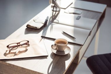 selective focus of eyeglasses on clipboard, cup of coffee and office supplies at workplace