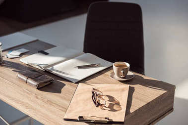 close-up view of eyeglasses on clipboard, cup of coffee and office supplies at workplace