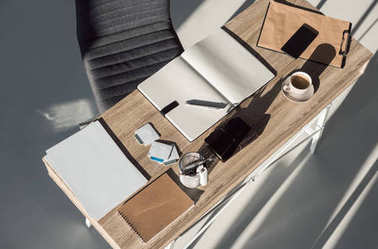 top view of blank notebooks, cup of coffee and smartphone on table in office