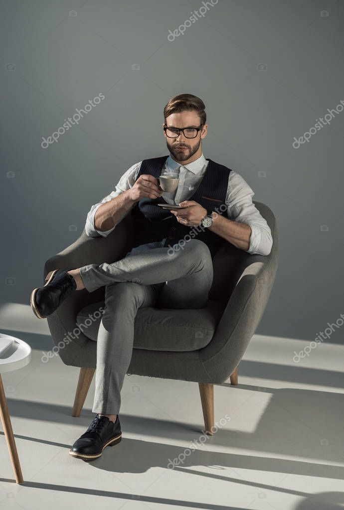 full length view of stylish businessman with cup of coffee looking at camera