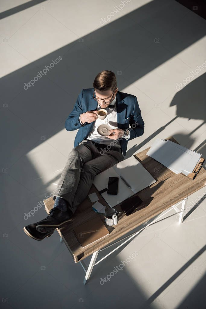 high angle view of stylish young businessman in eyeglasses drinking coffee at workplace