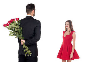 rear view of boyfriend hiding bouquet of roses from girlfriend isolated on white