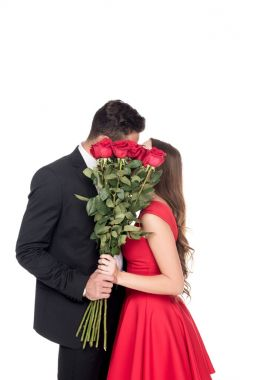 heterosexual couple kissing and covering faces with bouquet isolated on white