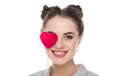 smiling girl covering eye with paper heart isolated on white, valentines day concept