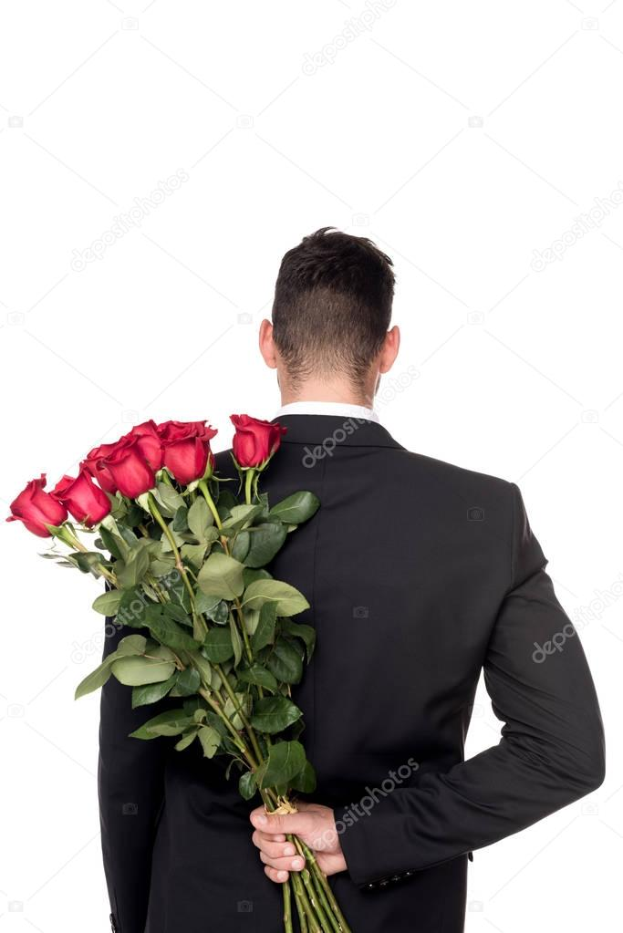 rear view of man hiding bouquet of roses isolated on white