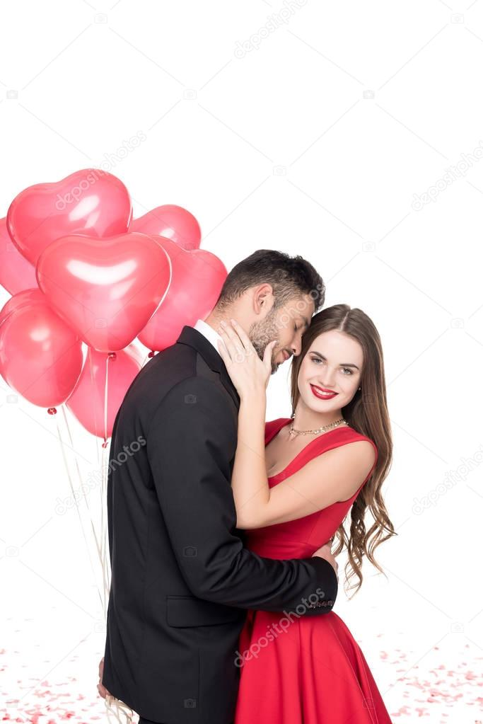 boyfriend with heart shaped balloons hugging girlfriend isolated on white, valentines day concept