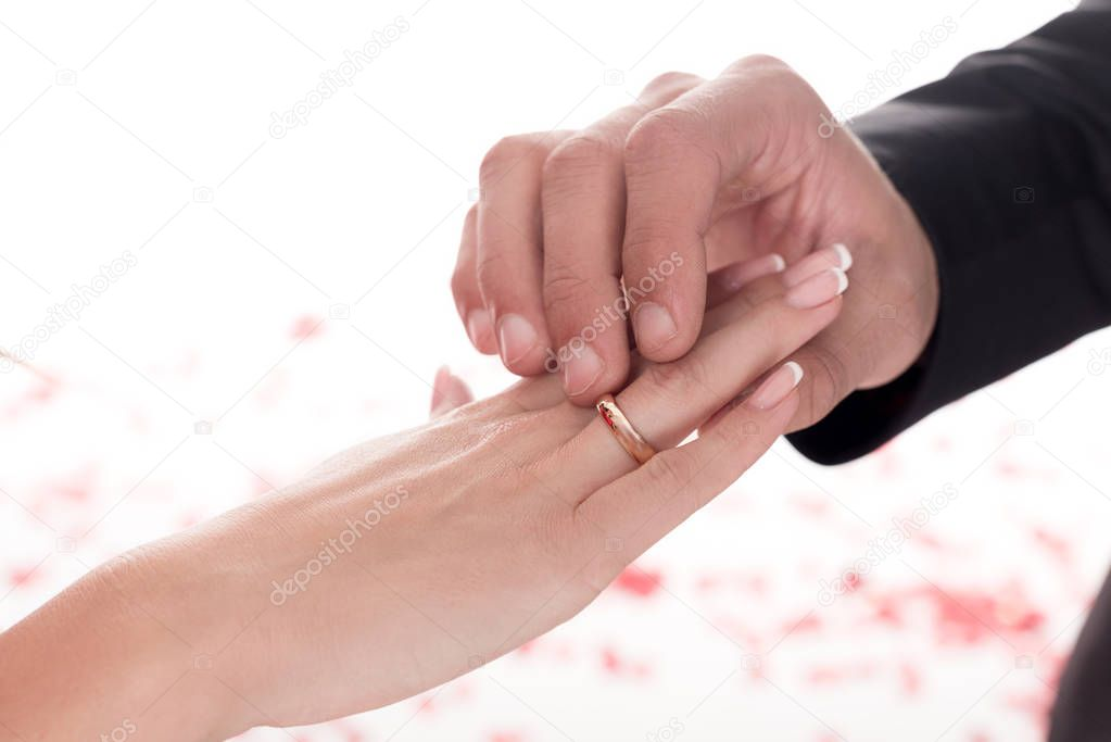 cropped image of boyfriend wearing ring on girlfriends finger isolated on white, valentines day concept
