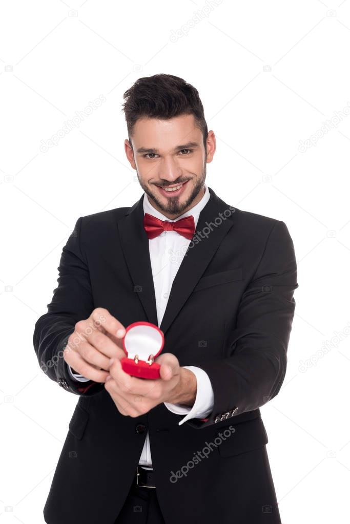 handsome man showing red box with marriage rings isolated on white