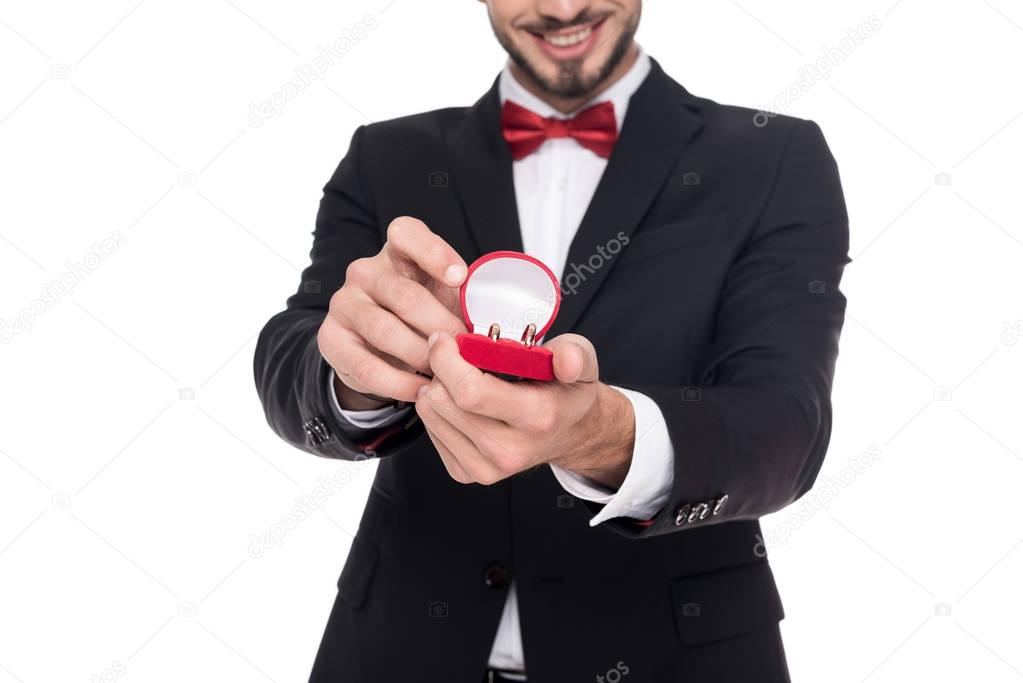 cropped image of handsome man showing red box with marriage rings isolated on white
