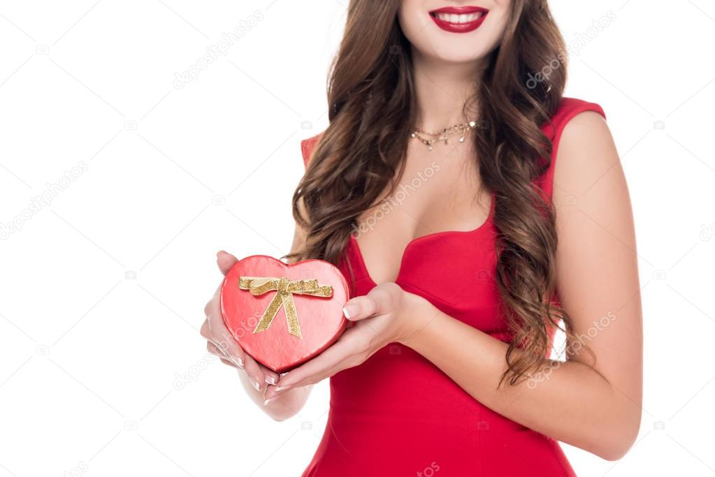cropped image of smiling girl in dress holding present box isolated on white, valentines day concept