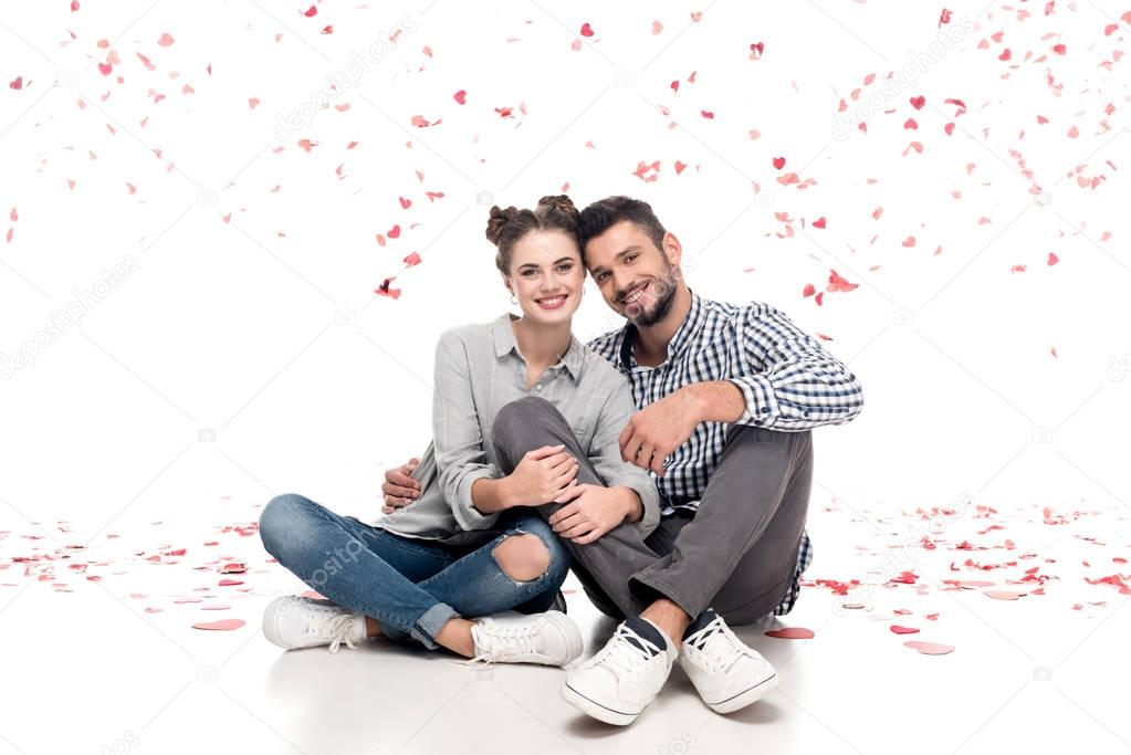happy couple sitting under falling confetti and hugging on white, valentines day concept