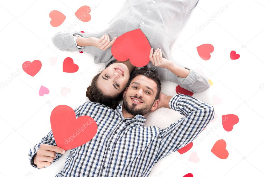 overhead view of couple lying with paper hearts isolated on white, valentines day concept