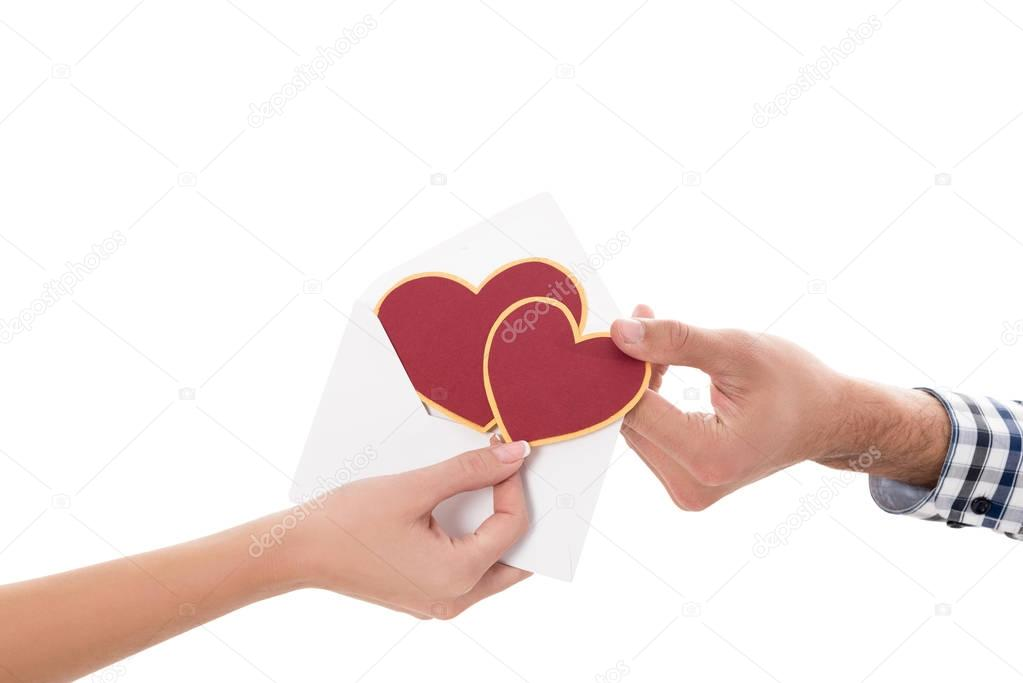 cropped image of couple holding valentines postcard isolated on white